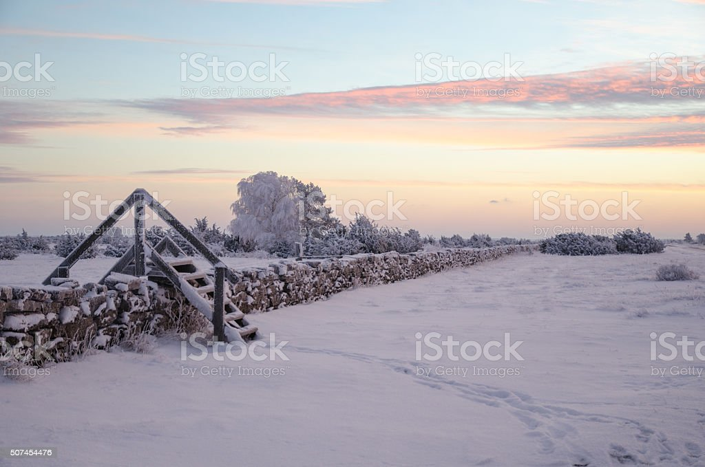 Dawn at a winterland with a stile by stone wall stock photo