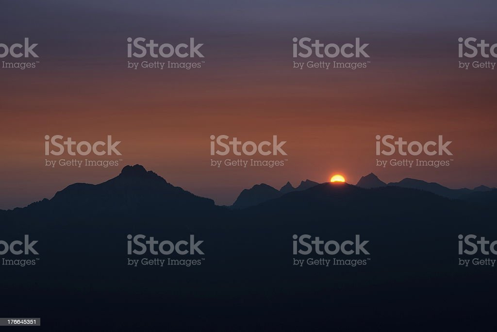 dawn with orange ball of sun appearing behind mountain chain royalty-free stock photo