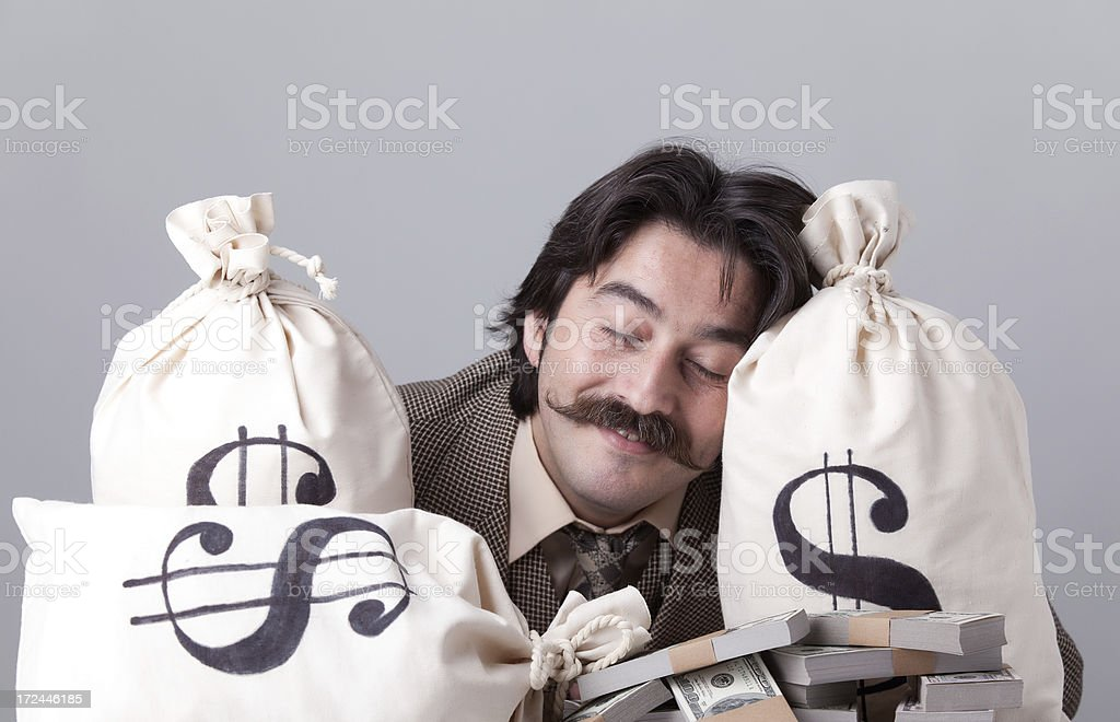 Day dreaming man on money bags royalty-free stock photo