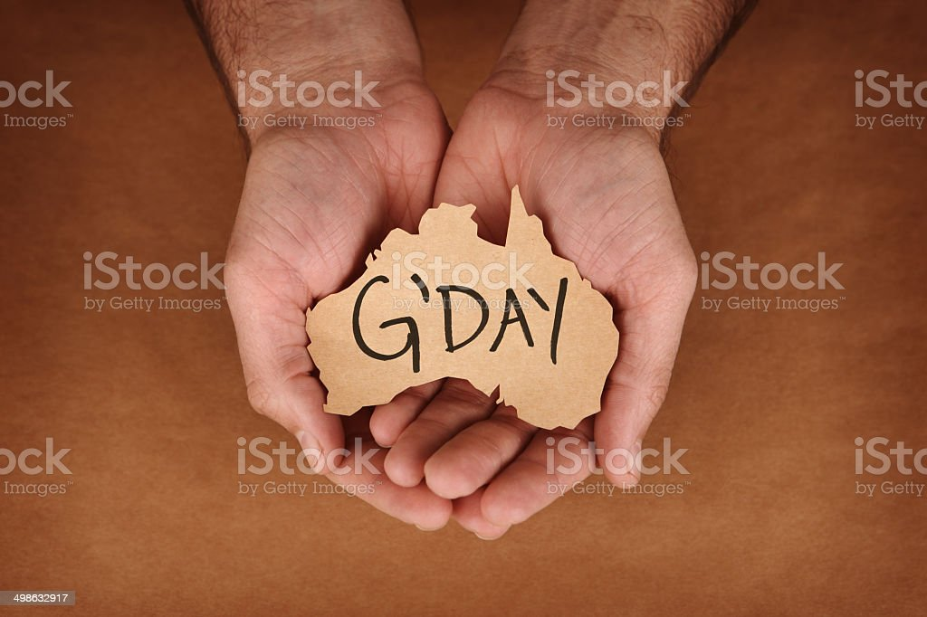 G'Day Written on Brown Paper Australia Shape in Hands stock photo