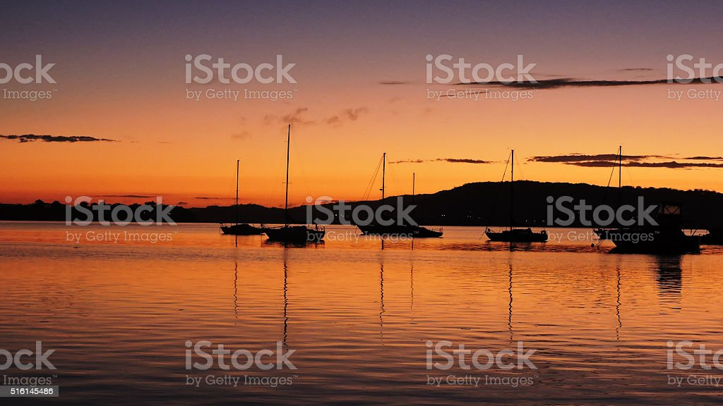 Daybreak waterscape with boats and reflections stock photo