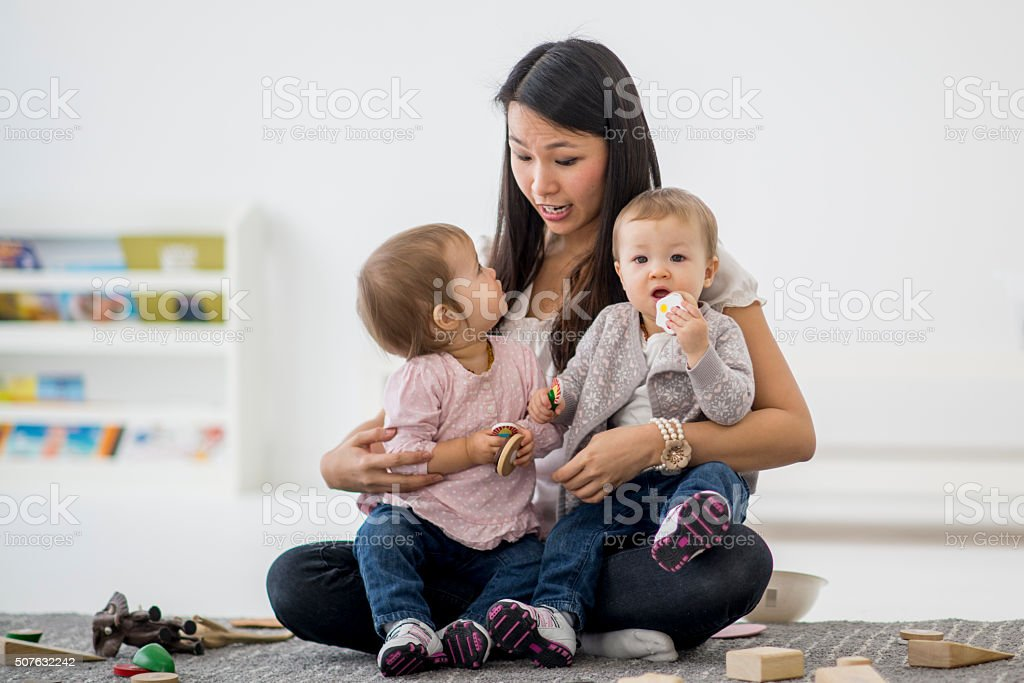 Daycare teacher playing with twin sisters. stock photo