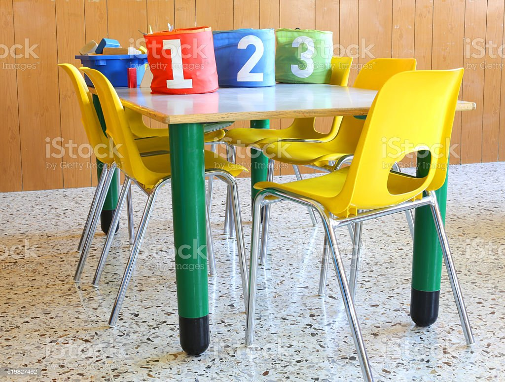 daycare with numbered jars and small yellow chairs stock photo