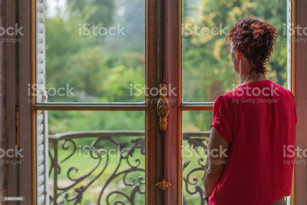 Daydreaming while looking out a window to a lush garden stock photo