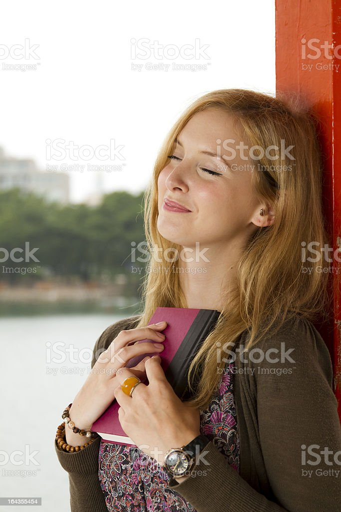 Daydreaming Young Woman Holds Book Close to Her Chest royalty-free stock photo