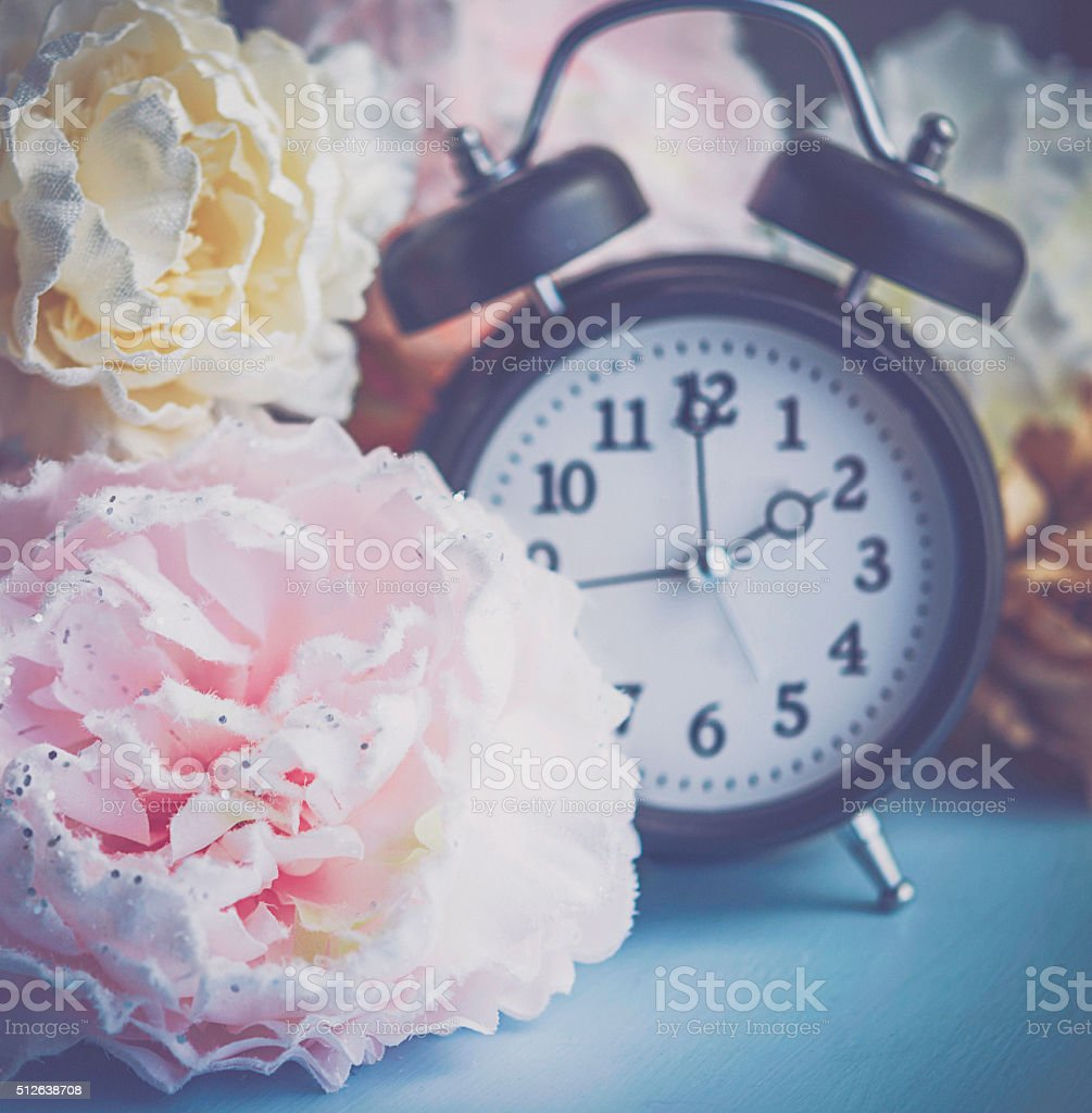 Daylight saving time. Clock with spring blooms stock photo