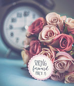 Daylight saving time. Clock with spring blooms