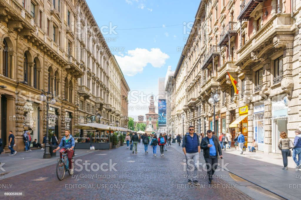 Daytime of architecture of the via Dante of Milan and a tourist on street with Sforzesco Castle in a background with blue sky in Milan, Italy. stock photo