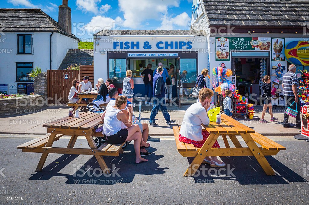 Daytrippers on seaside holidays beside fish and chip shop England stock photo