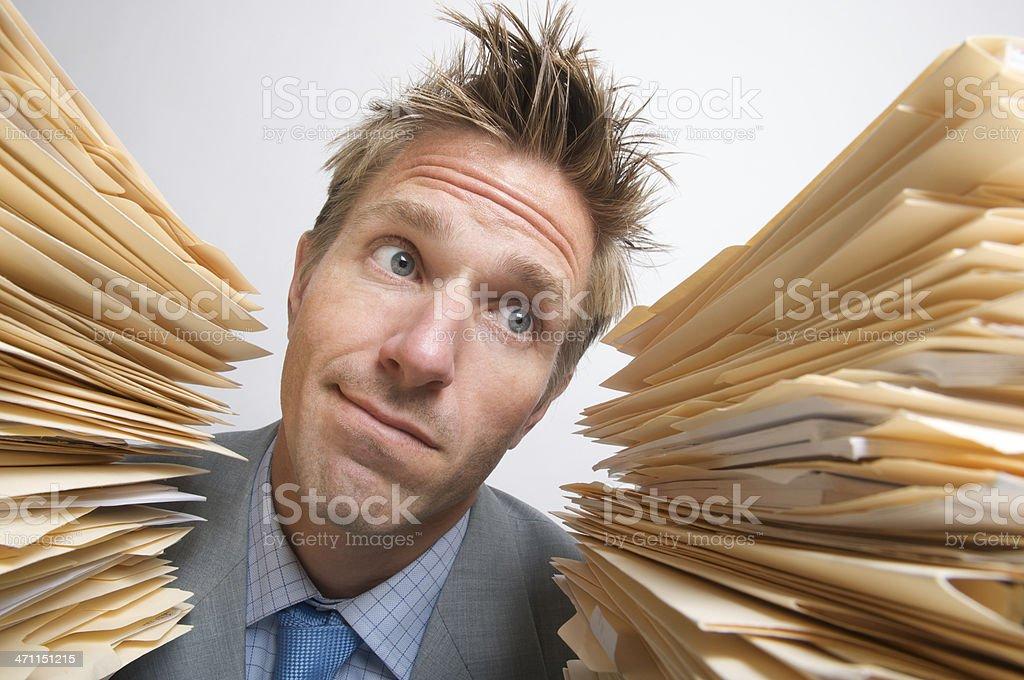 Dazed Businessman Office Worker Between Stacks of Files stock photo