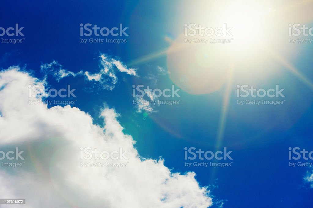 Dazzling midday sun in lightly clouded sky stock photo
