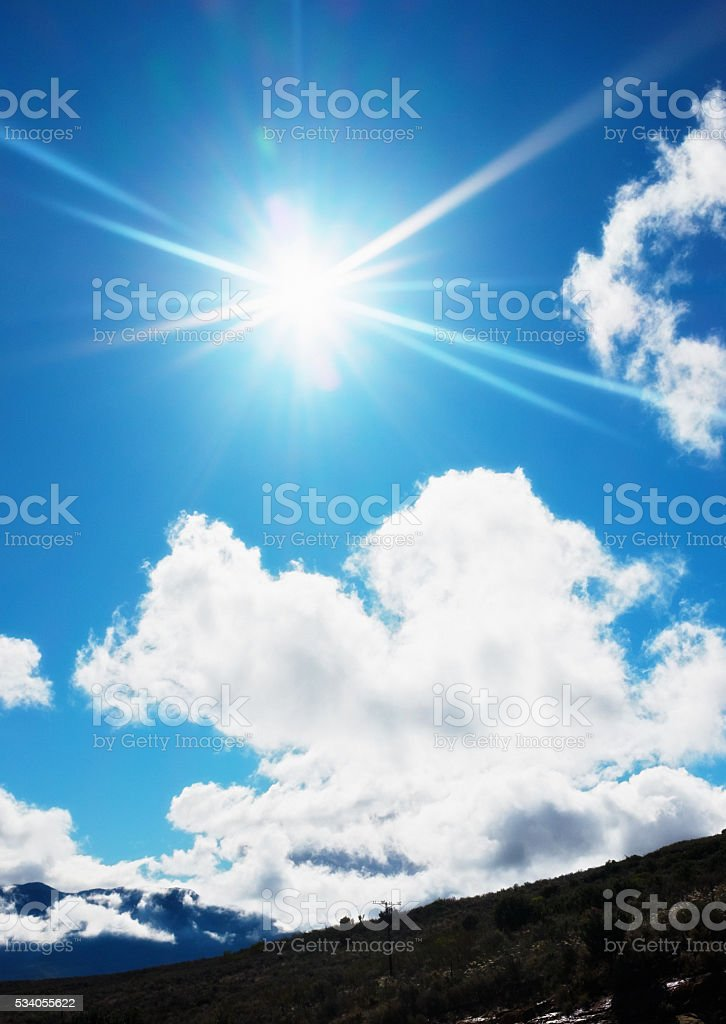 Dazzling noonday sun radiating in bright blue, lightly clouded sky stock photo