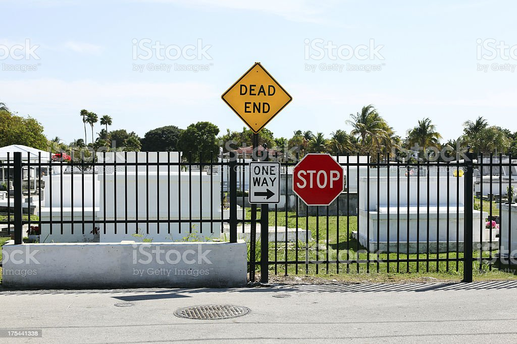 Dead end, stop, one-way signs on cemetery fence. stock photo