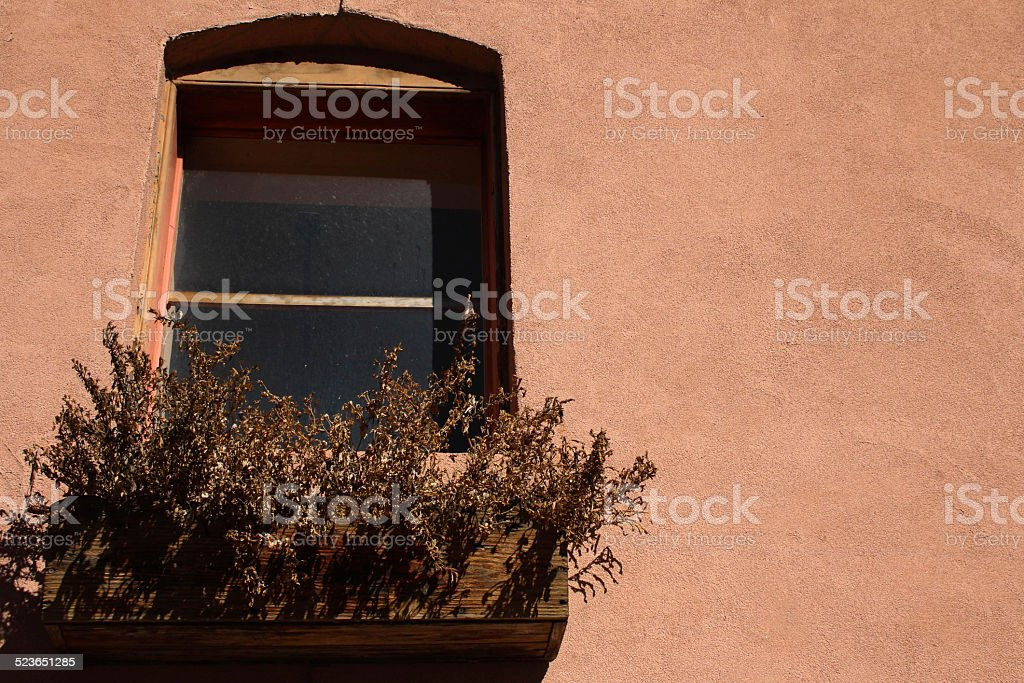 Dead flowers in a window box and pink stucco stock photo