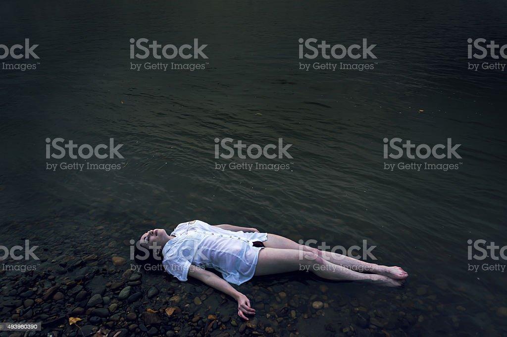 dead girl lying on the rock stock photo
