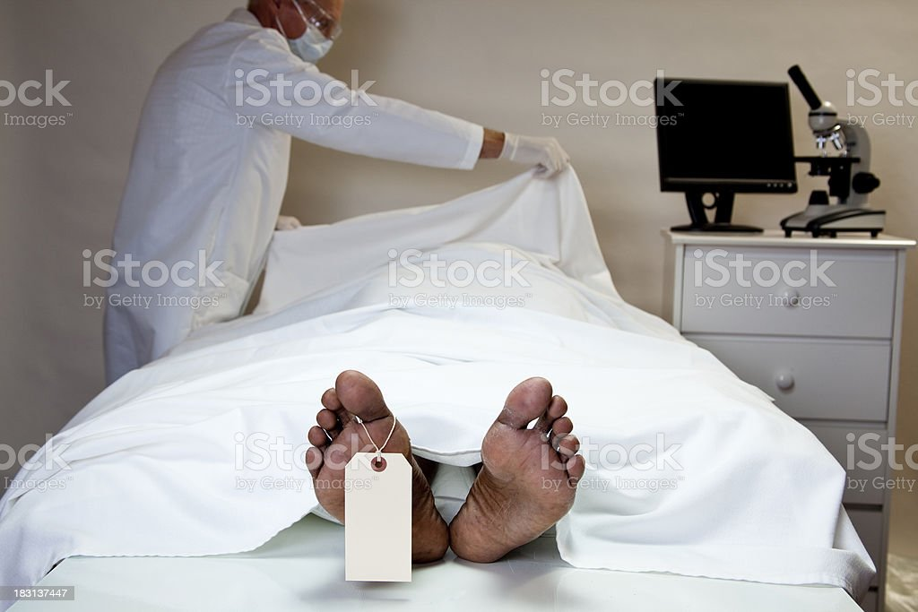 Dead man in morgue, coroner covers up body, toe tag. stock photo