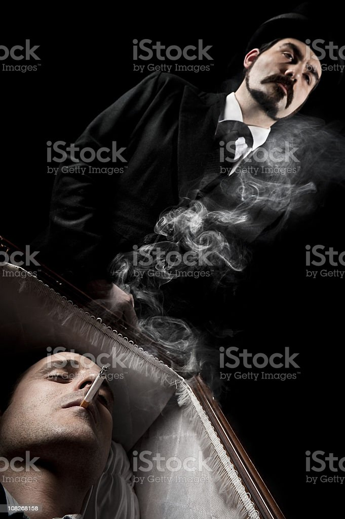 Dead man smoking in the coffin stock photo
