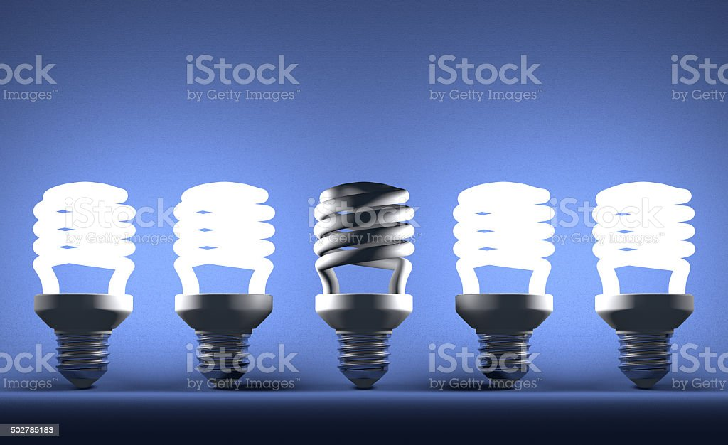 Dead spiral lightbulb in row of glowing ones on blue stock photo
