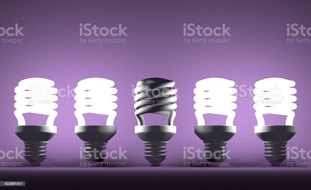 Dead spiral lightbulb in row of glowing ones on violet stock photo