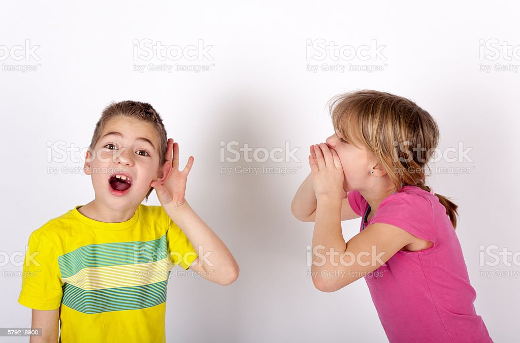Small boy cupping his ear cant hear his sister shouting