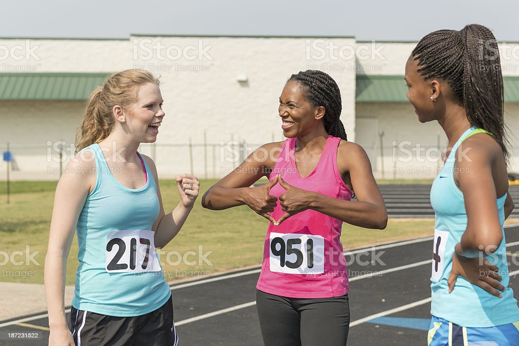 Woman of african descent signing \'trophy\' while with two other track...