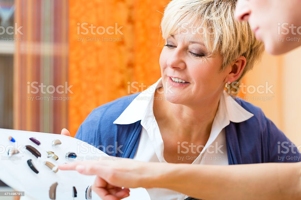 Deaf woman works on creating a hearing test with a man stock photo