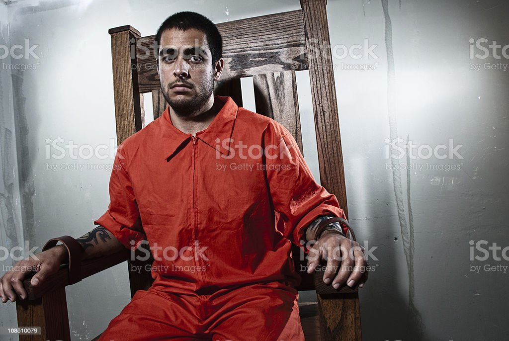 A young hardened criminal is strapped into the electric chair and...