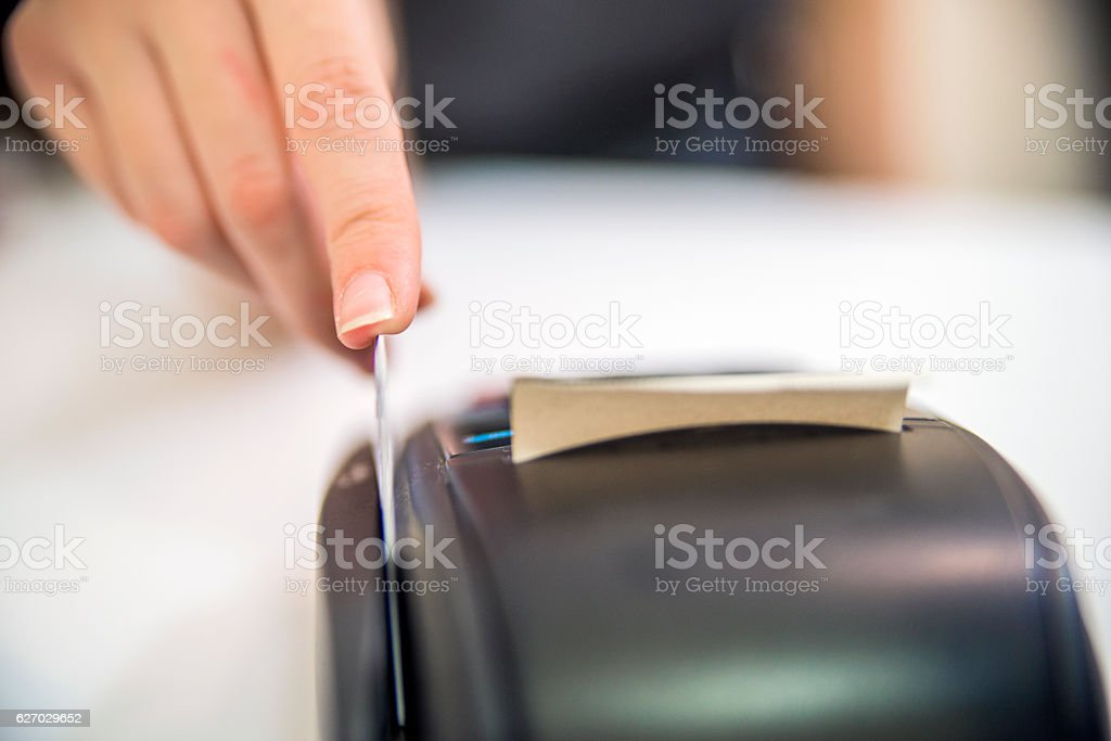 Debit card swiping on pos terminal. credit card reader machine stock photo