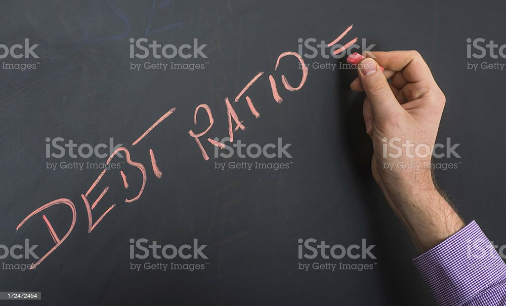 debt ratio on blackboard with hand stock photo