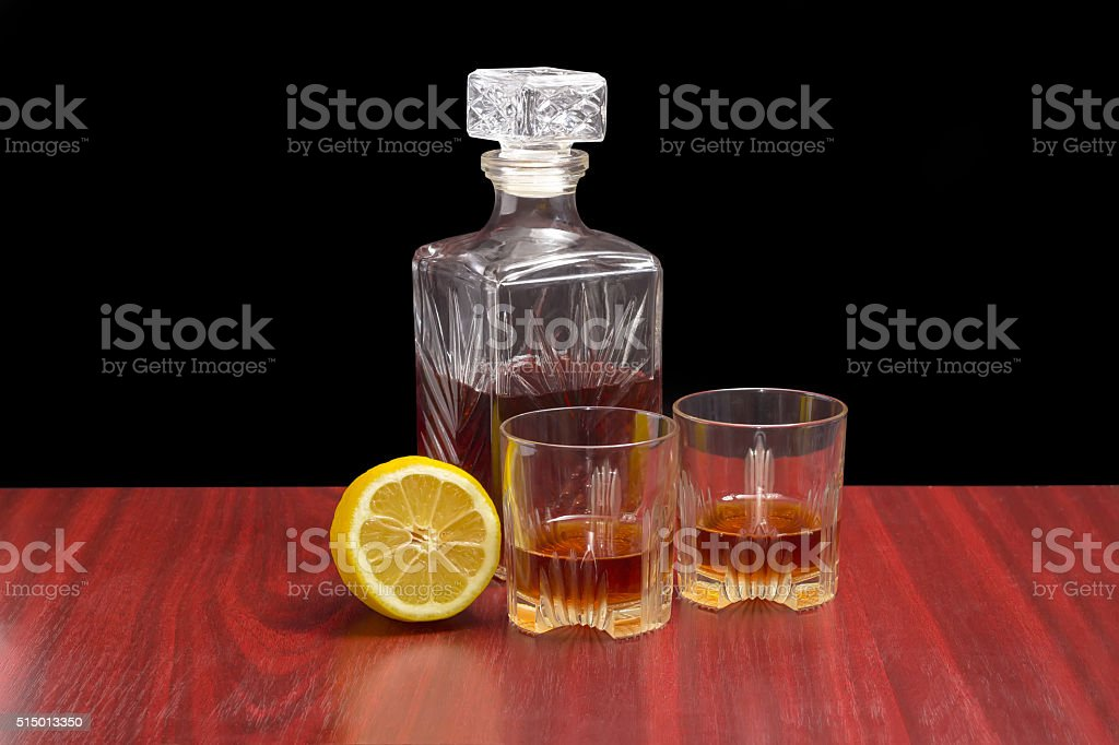 Decanter and two glasses with whiskey and lemon stock photo