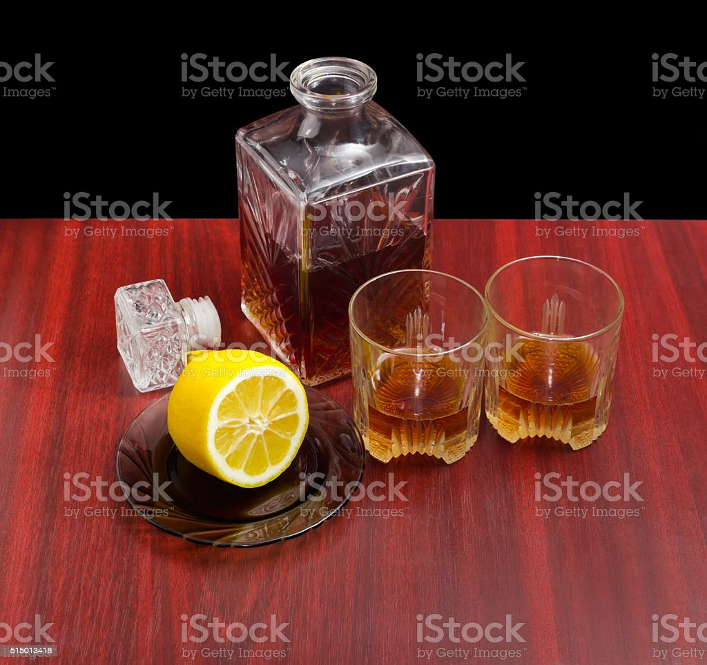 Decanter and two glasses with whiskey, lemon on a saucer stock photo