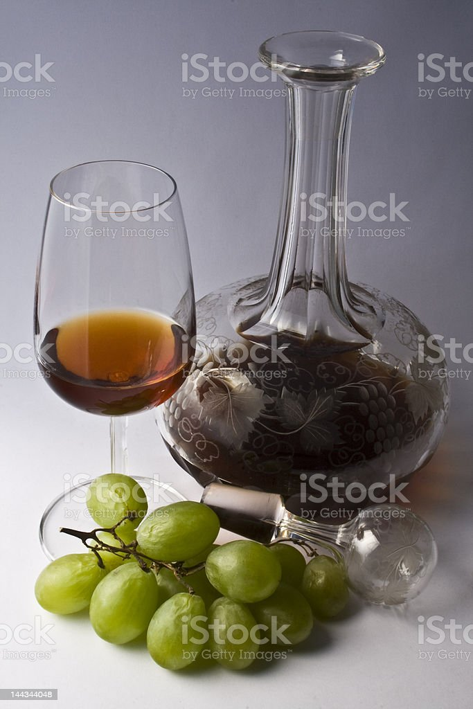 Decanter, glass of wine, and grapes on gray stock photo