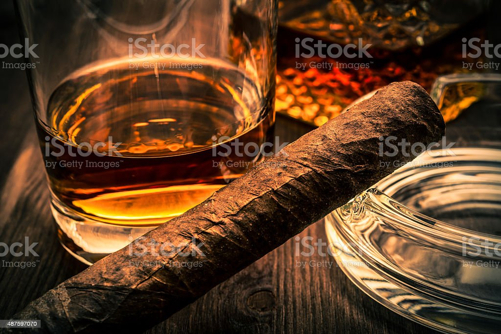 Decanter of whiskey and a glass with cuban cigar stock photo