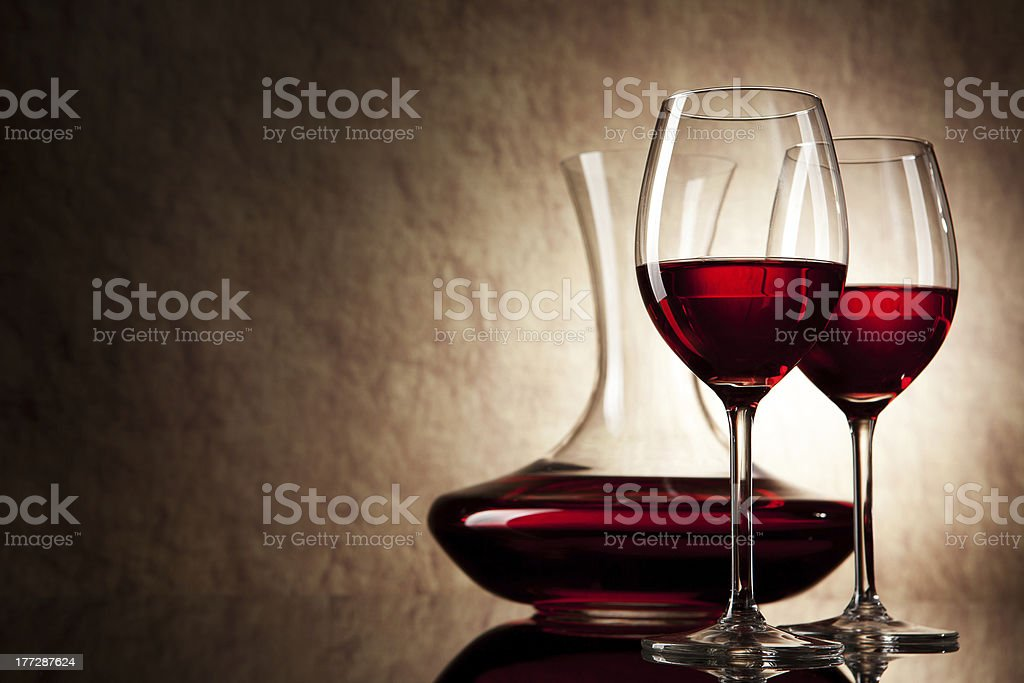 decanter with red wine and glass on a old stone background stock photo