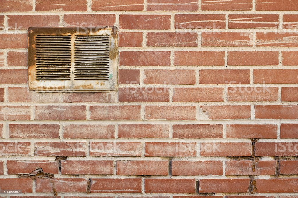 Decayed Brick Wall and Vent. stock photo