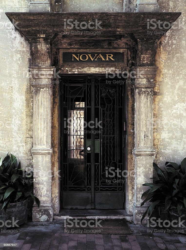 Decaying City Door with metal gate and ornate columns royalty-free stock photo