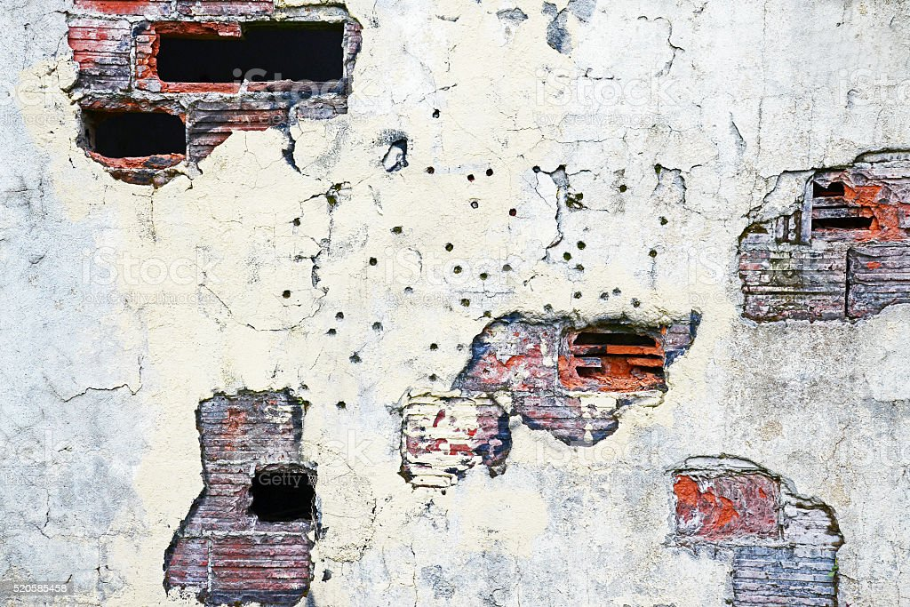 Decaying wall riddled with bullet holes stock photo