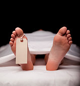 Deceased Person Laying on Table with Toe Tag Attached
