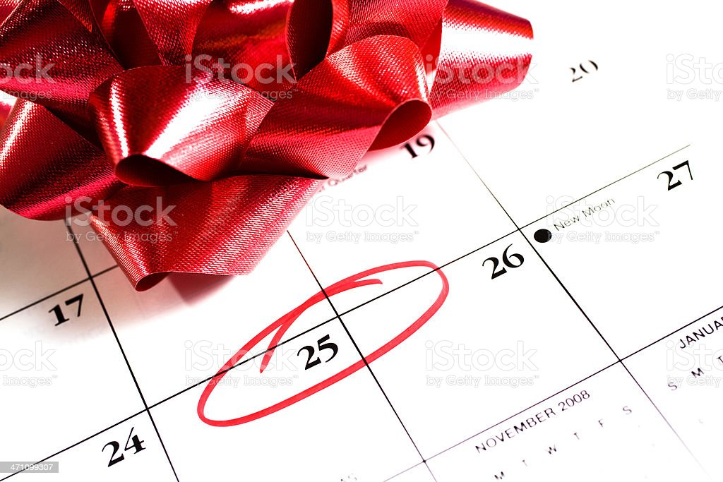 December calendar 25th circled, red gift bow for Christmas stock photo