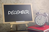 December on chalkboard with alarm clock.