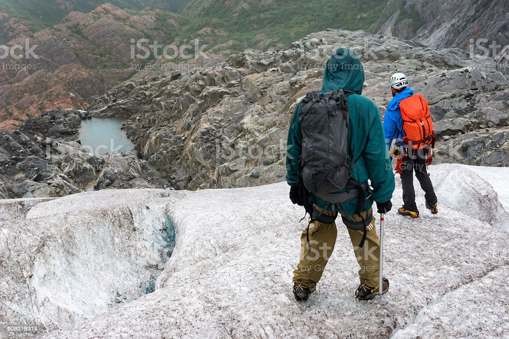 Deciding safest way down icy glacier terminus stock photo