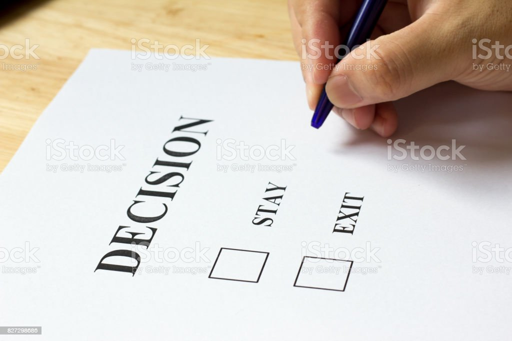 Decision paper with stay and exit choice on wood background stock photo