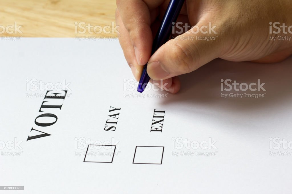 Decision paper with stay and exit choice with man held the pen on wood background stock photo