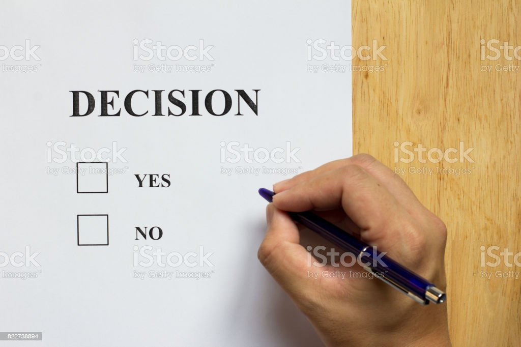Decision paper with yes and no choice with man hold the pen on wood background stock photo