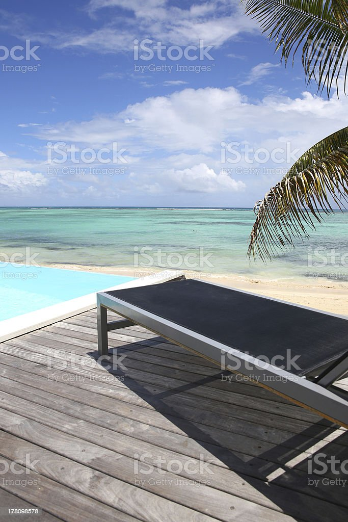 Deck chair on a swimming pool near the sea royalty-free stock photo