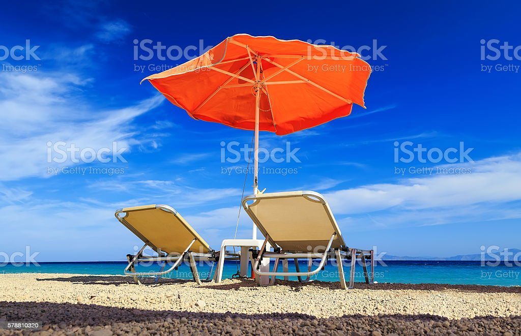 deck chairs and umbrella on background of sea and pebbles stock photo