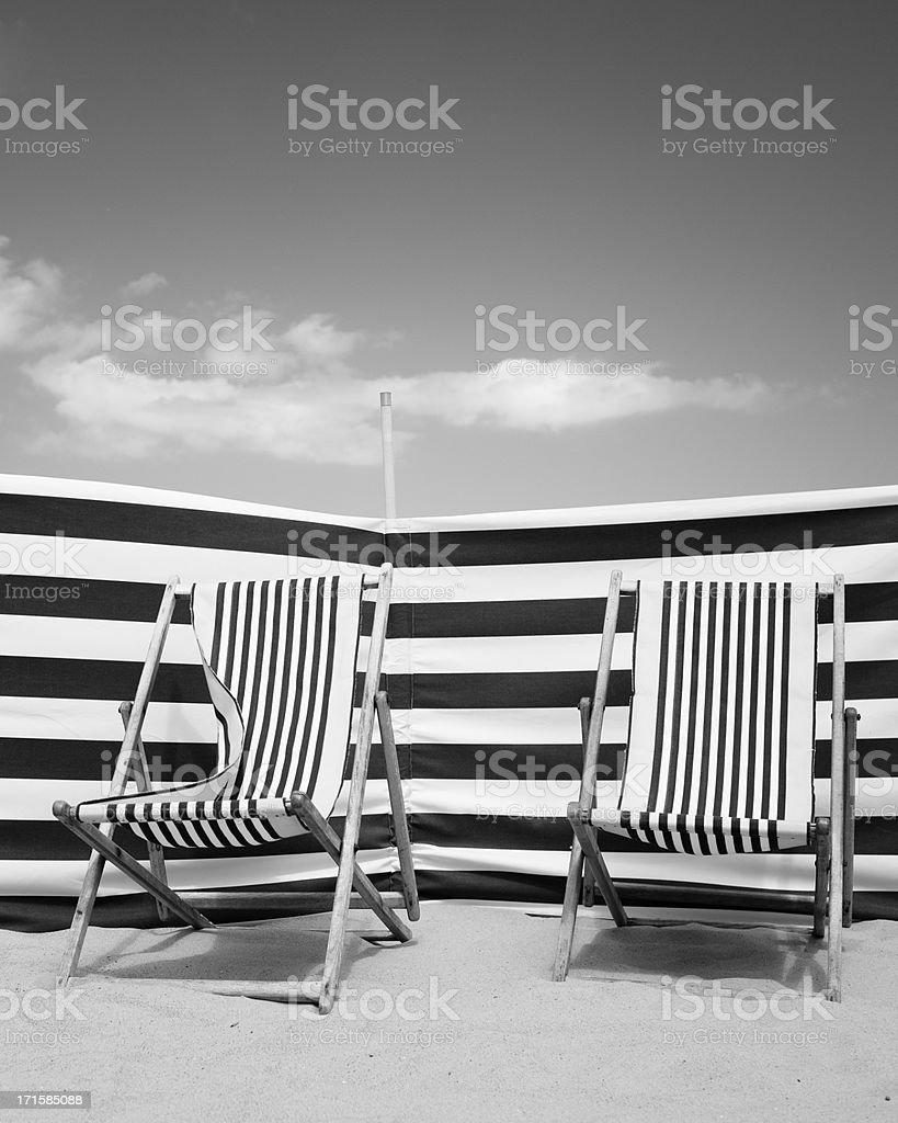 Deck Chairs and Windbreak on Sandy Beach royalty-free stock photo