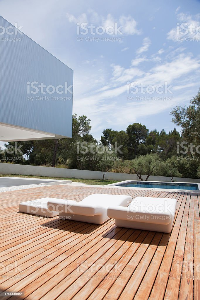 Deck chairs on patio of modern house royalty-free stock photo