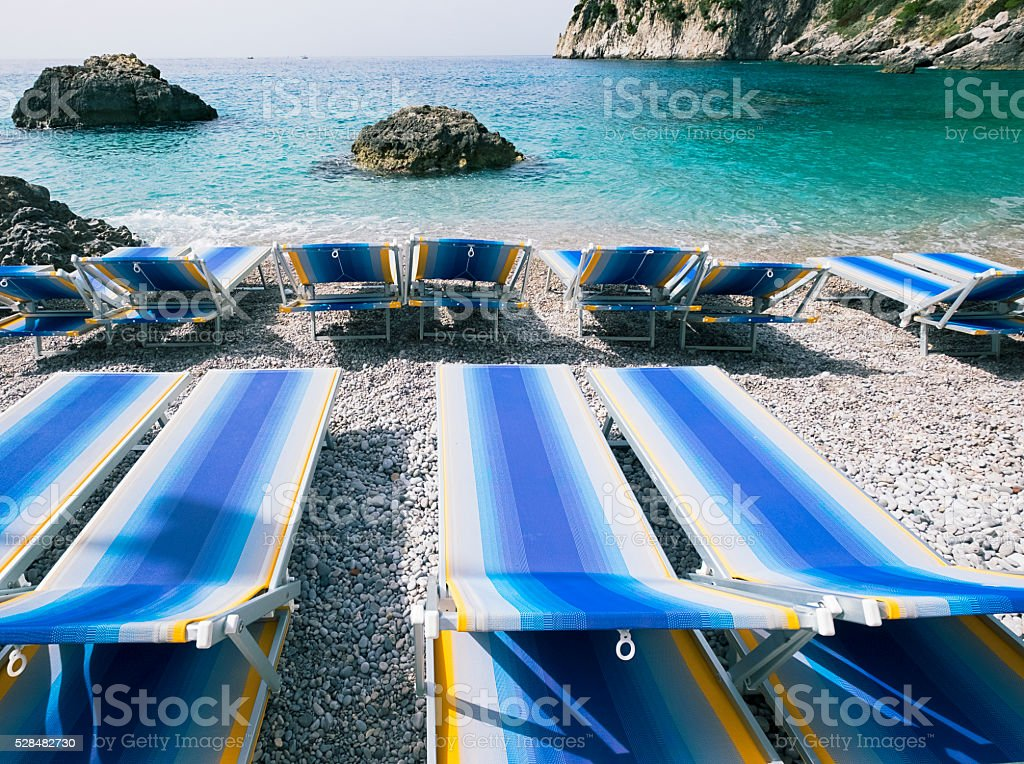 Deck chairs on rocky beach stock photo