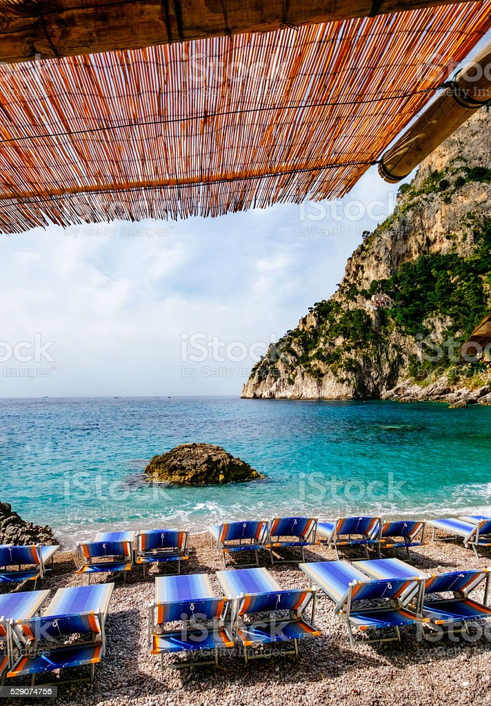 Deck chairs on the rocky beach stock photo